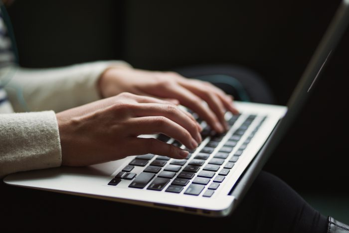 Blogger's hands typing on a laptop