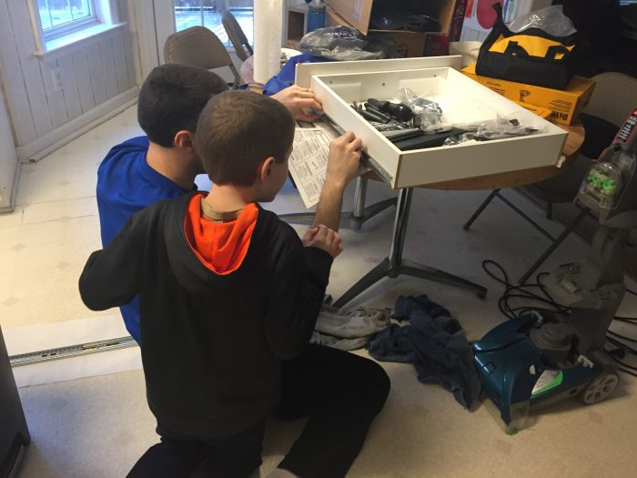 Andrew and his son examine a broken kitchen drawer