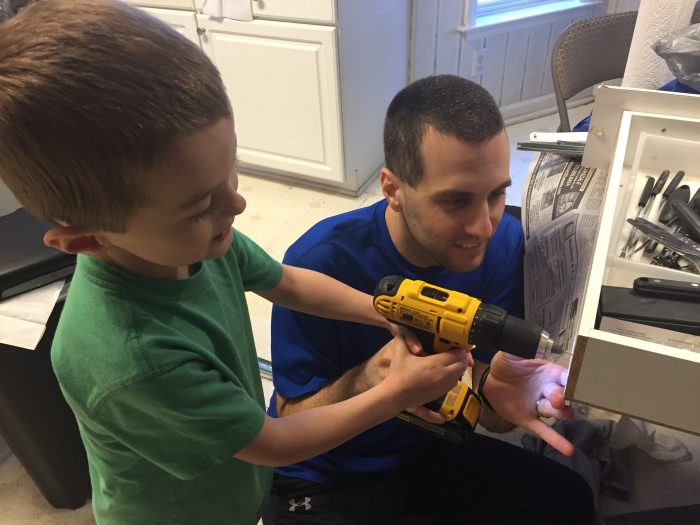 Andrew and his son use a drill to attach the slider to the drawer