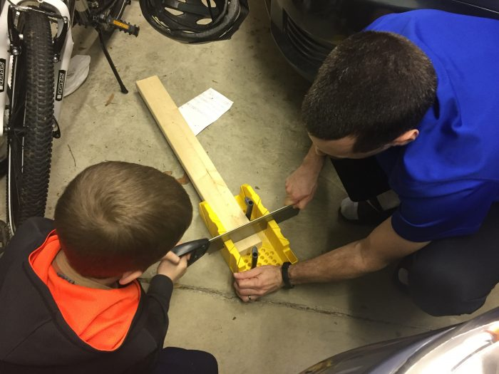 Andrew and his son use a mitre saw to cut a new wooden shim